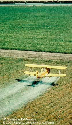 Aerial spraying of a crop field.